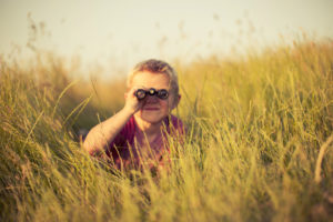 Young Boy Looking Through Binoculars Hiding in Grass